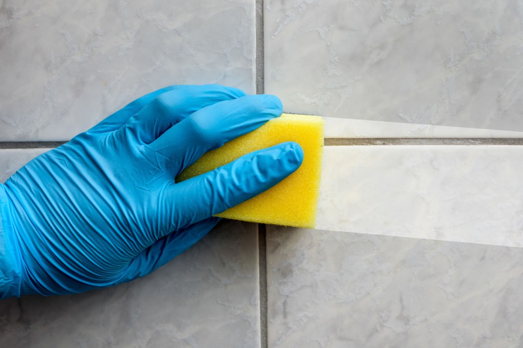 Cleaning sponge held in hand while cleaning bathroom with french lettering nettoyage